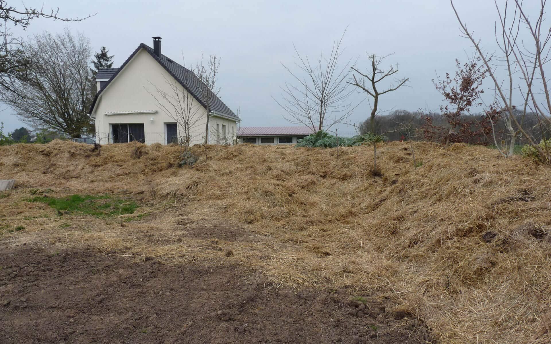 Buttes en périphérie du terrain couvertes de broyat de bois et de foin