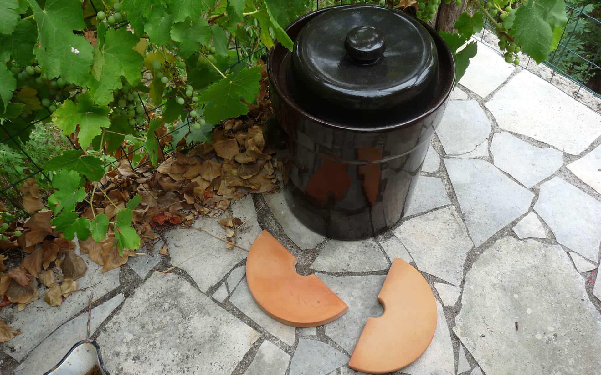 Pot en grès avec joint hydraulique et ses pierres d'appui pour tasser la préparation lacto fermentée.