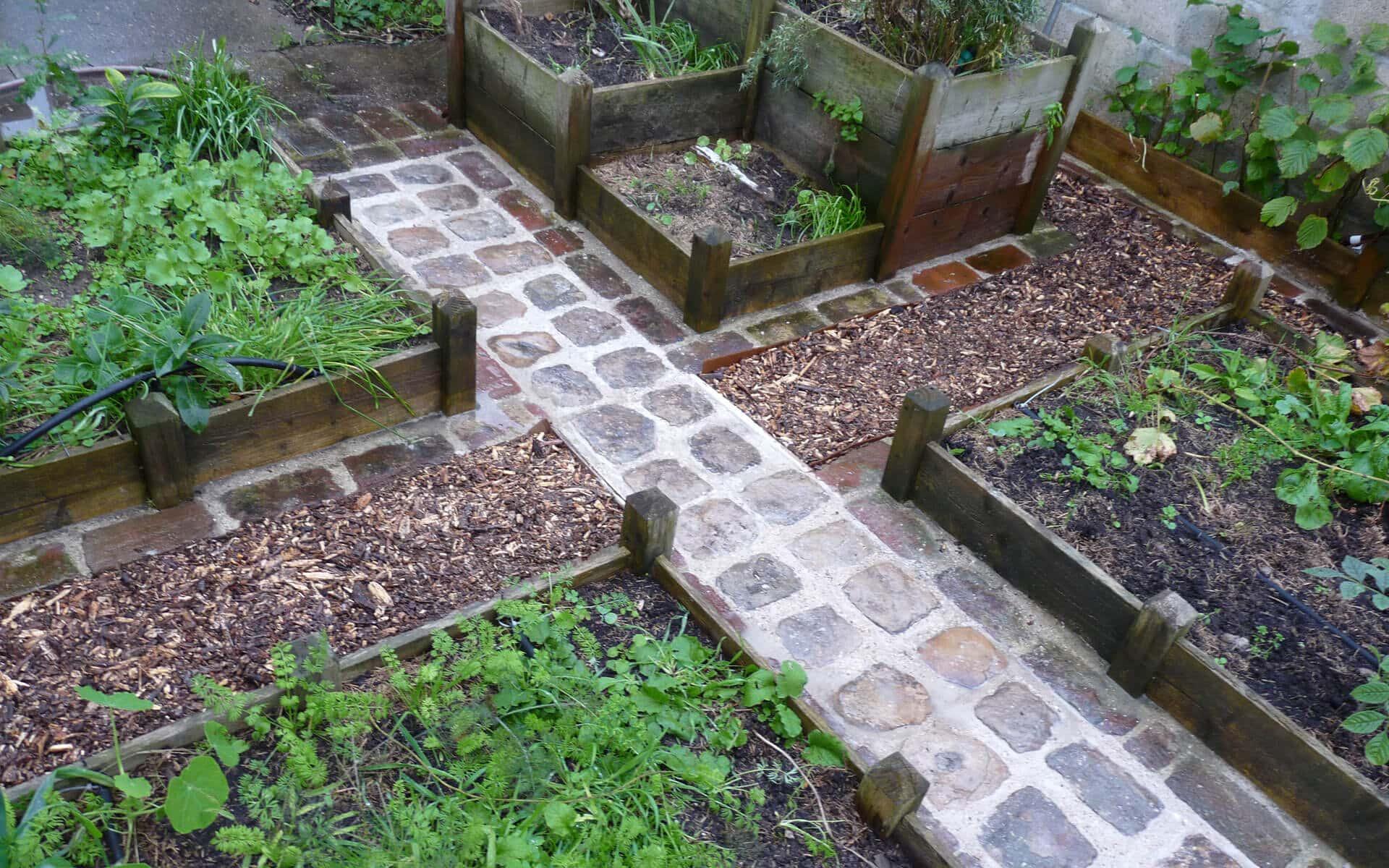Le potager en carrés donne l'occasion de réaliser différents type d'allées : ici des pavés et du broyat de bois.